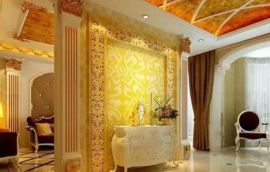 玄關玻璃隔斷效果圖   白色瓷磚拼花的玄關地面,搭配白色石膏線條圍成的吊頂,點綴著金黃色貴氣裝扮,讓人仿佛進入了一個皇宮。白色復古典雅印花祭祀桌臺,上面擺放著一盆花與一支蠟燭。背景墻是金碧輝煌的裝修效果,雕花外框,搭配金色印花壁紙鋪貼,帶來宮廷式的享受。